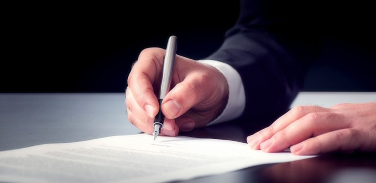 hand of a man in a suit writing in a piece of paper