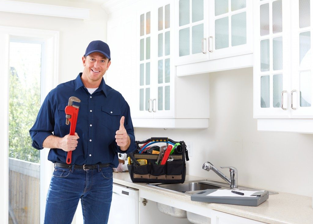 repair man with bag of tools in the kitchen