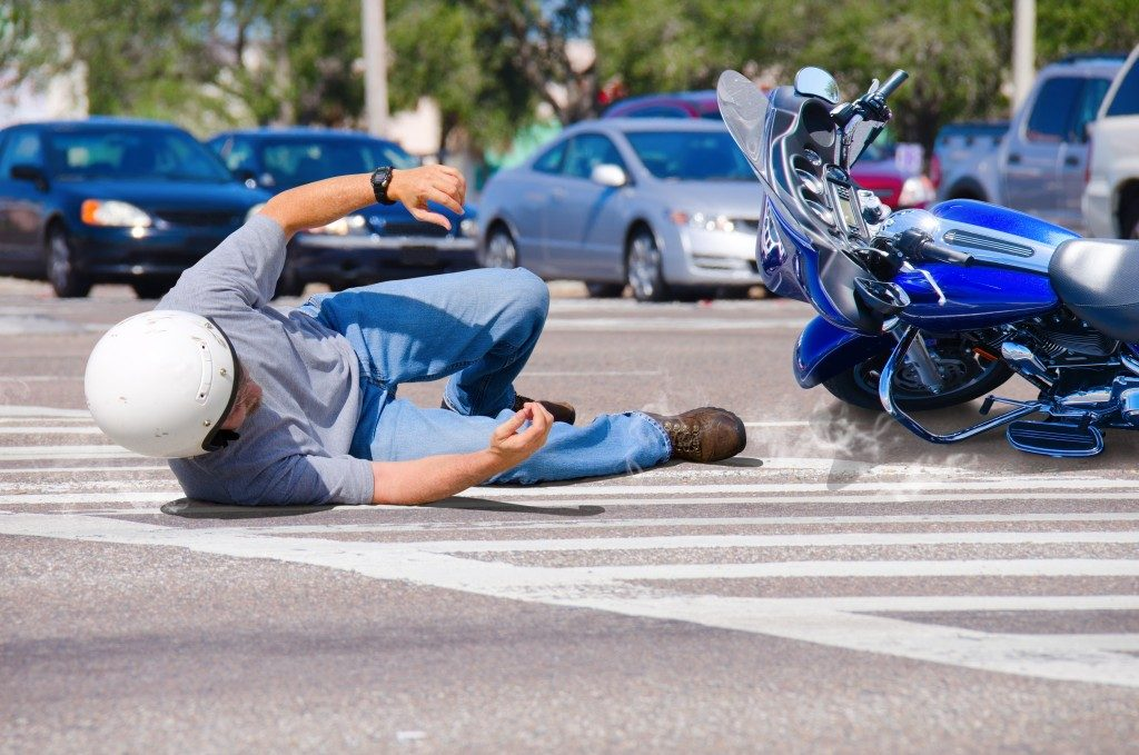 Motorcycle rider has wrecked and is laying in the road as his motorcycle goes sliding into the busy intersection.