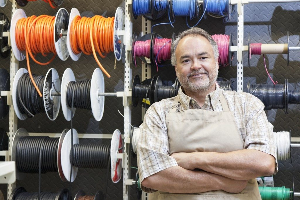 man smiling by the wire spools