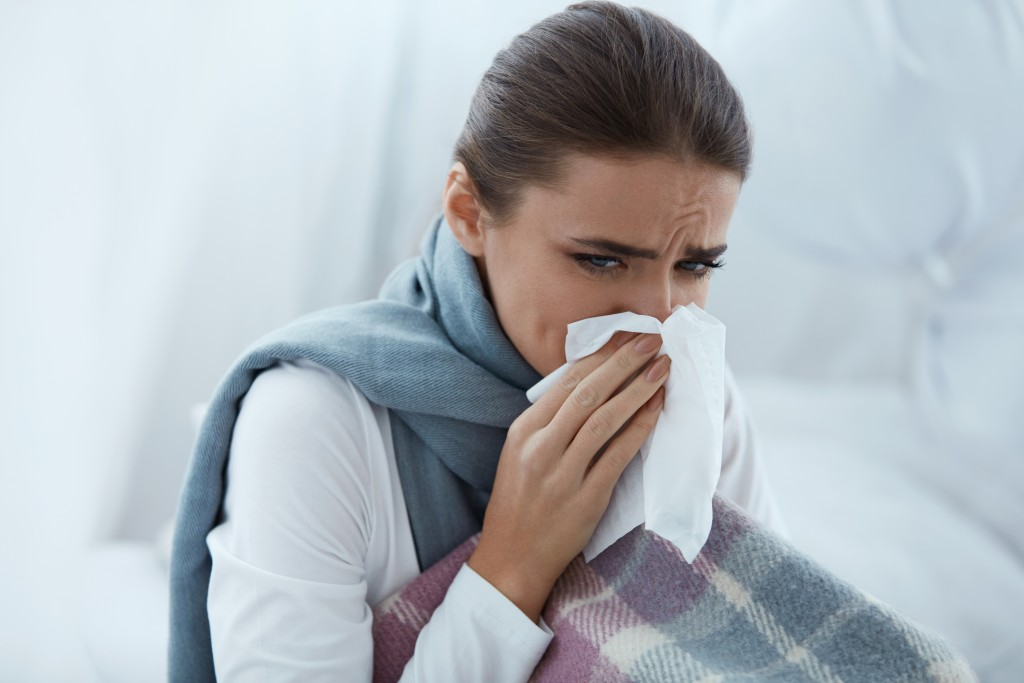 Female with colds blowing her nose