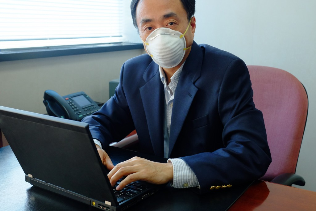 Asian businessman wearing protective mask in an office with air pollution