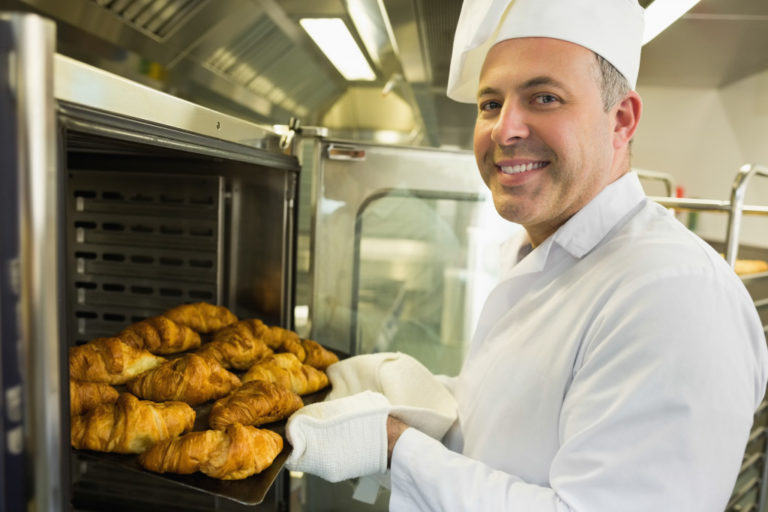 baker putting his breads in the oven